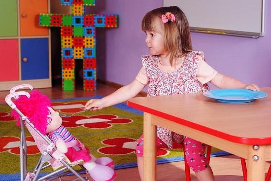 Fetita ce se joaca cu papusa