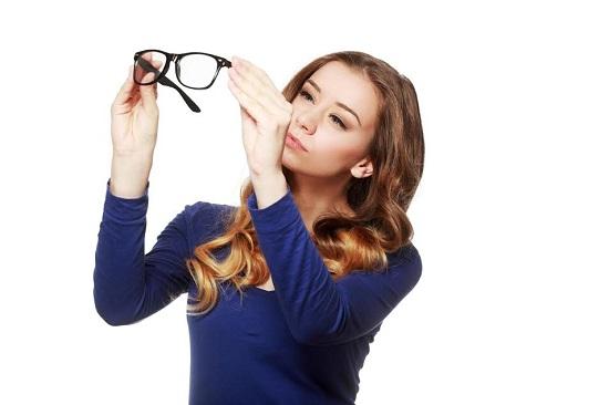 Fata ce se uita la o pereche de ochelari