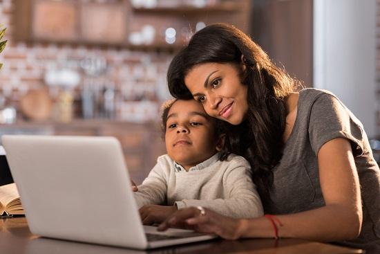 Mama si fiica ce stau in fata computerului