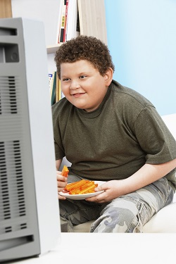 Copil obez, ce sta la televizor si mananca