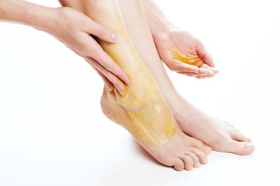 Femeie ce isi unge picioarele cu miere