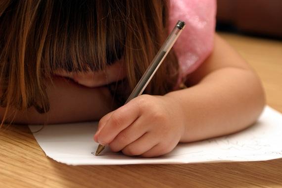 Fetita care scrie cu stanga