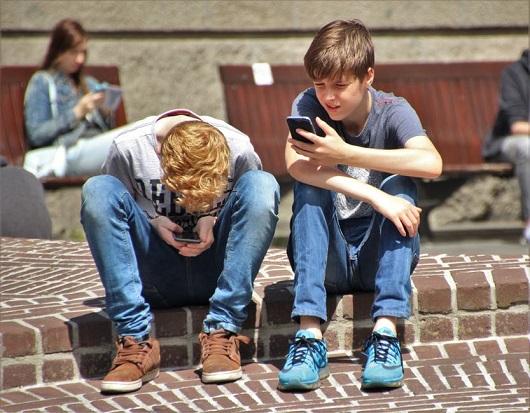 Adolescenti ce se uita pe telefoanele mobile
