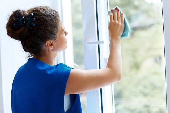 Femeie sterge fereastra cu o carpa