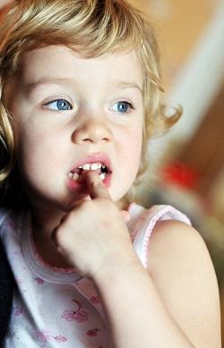 Fetita ce isi roade o unghie