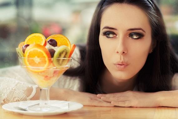 Fata ce se uita la o salata de fructe apetisanta