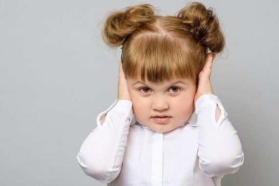 Fetita ce isi tine manutele la urechi