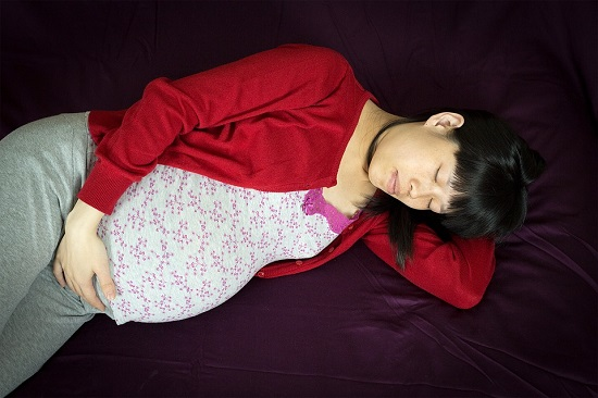 Femeie insarcinata dormind pe canapea