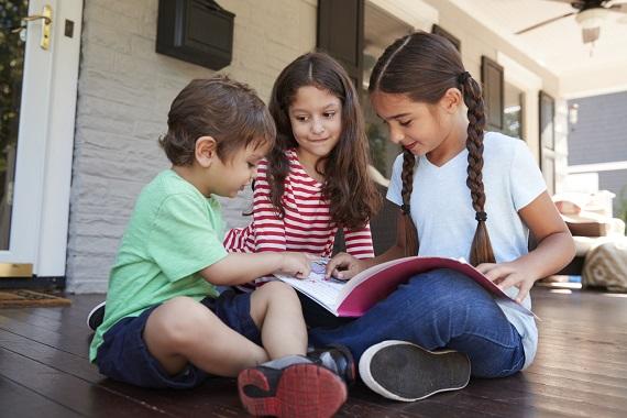 Trei copii ce se uita pe o carte