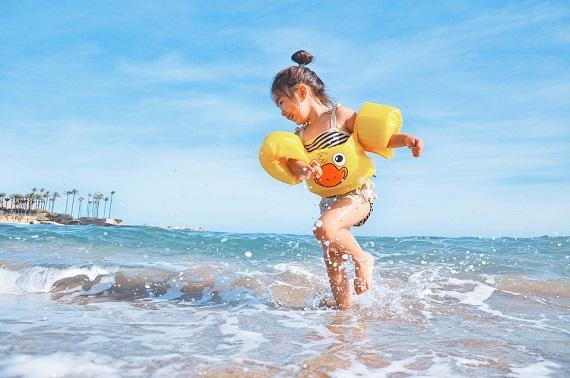 Fetita echipata cu pernute gonflabile de plutit pe apa