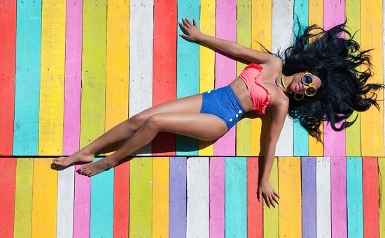 Fata ce poarta un costum de baie din doua piese, in culori indraznete