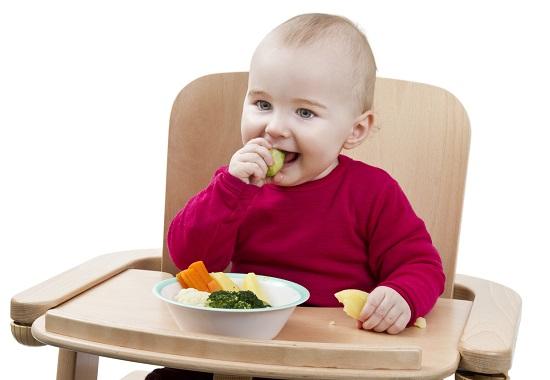 Bebelus ce mananca cu manuta legume fierte