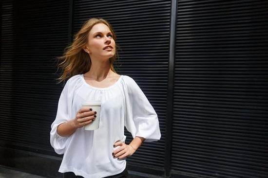 Femeie in bluza alba, cu o cafea sau  cu un ceai in mana