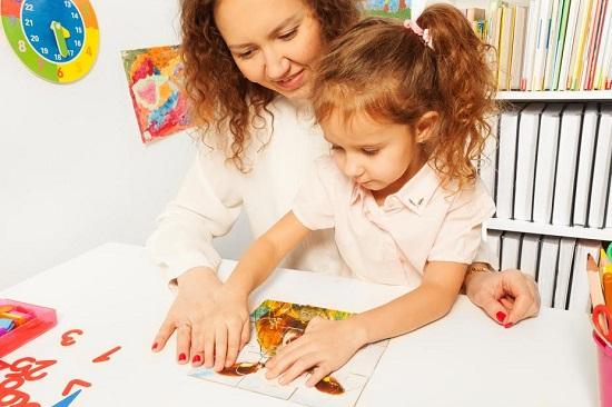 Fetita rezolva un puzzle, alaturi de mama ei