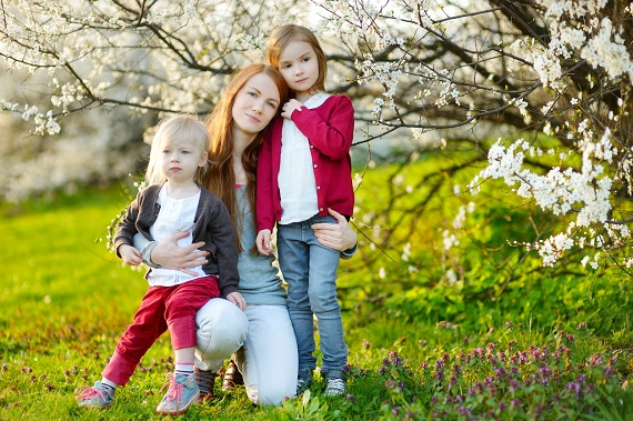 Mama alaturi de fiicele ei langa un arbore inflorit
