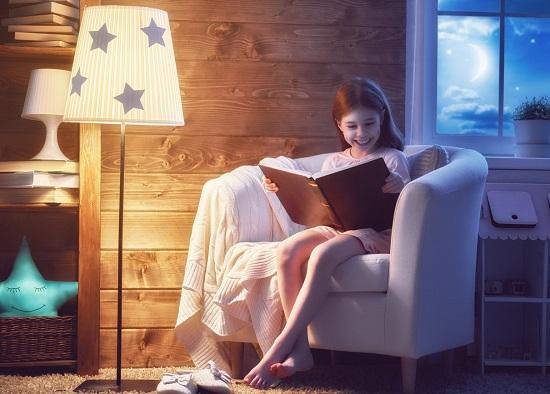 Fetita ce citeste seara, langa o lampa