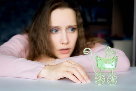 Femeie ce priveste insistent un carucior de copil in miniatura