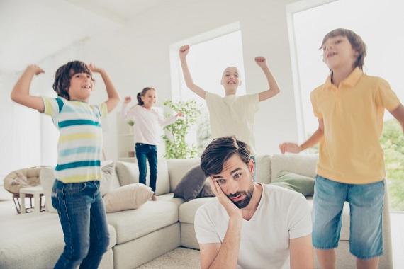 Copii ce se distreaza, in timp ce barbatul ce se afla in preajma lor este mai degraba disperat