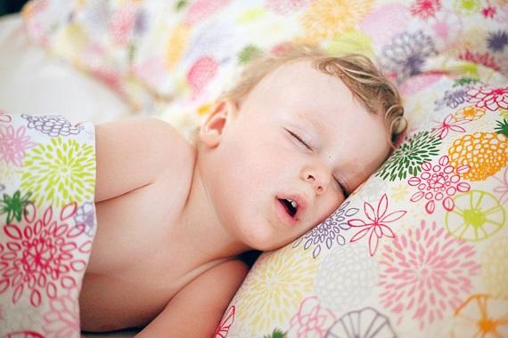Baietel ce doarme pe o parte