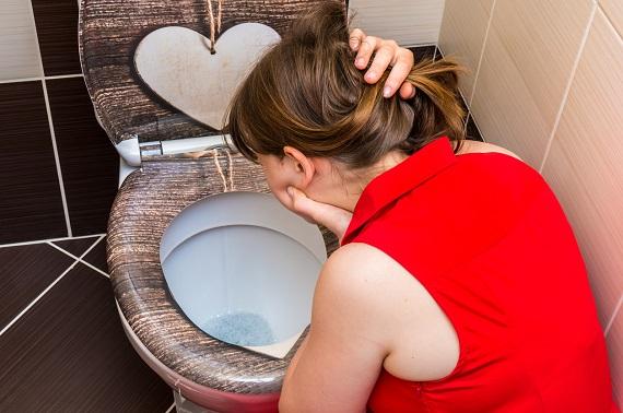 Femeie ce s-a aplecat asupra vasului de toaleta pentru ca vrea sa vomeze