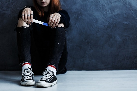 Adolescenta care tine in mana un test de sarcina