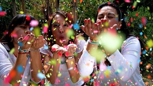 3 femei care sufla in confetti