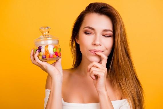 Fata ce se uita la un borcanel cu bomboane colorate