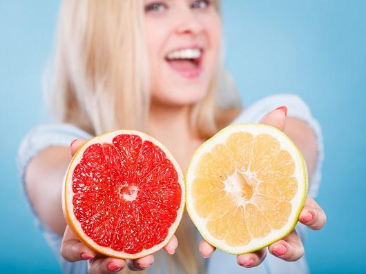 Fata ce tine in mana cate o jumatate de grapefruit