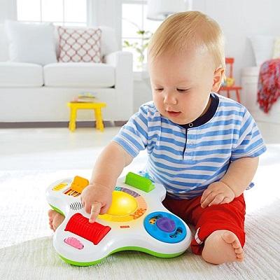 Bebelus apasand pe butonul unei jucarii de plastic