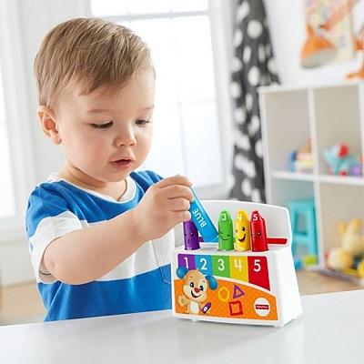 Bebelus se uita la niste creioane colorate cu fetisoare