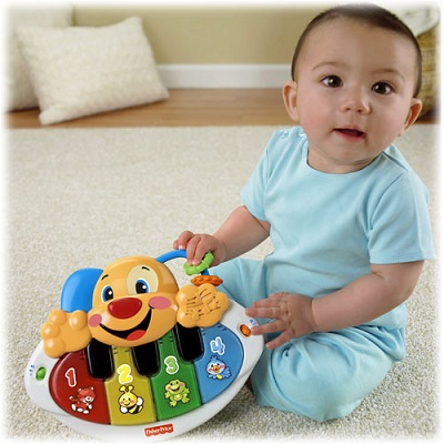 Bebelus cu un pian de jucarie