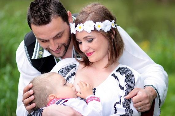 Femeie ce isi alapteaza bebelusul, in timp ce partenerul ei se uita cu drag la acesta