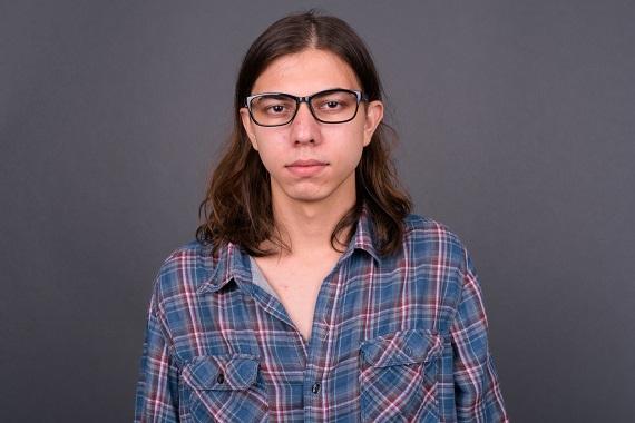 Adolescent cu par lung si ochelari