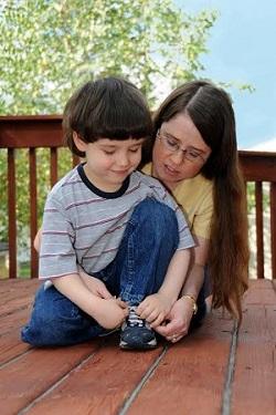 Mama sta cu copilul pentru a-l invata sa-si lege sireturile