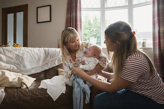 Femeie ce o ajuta pe ajuta pe alta sa aiba grija de bebelus