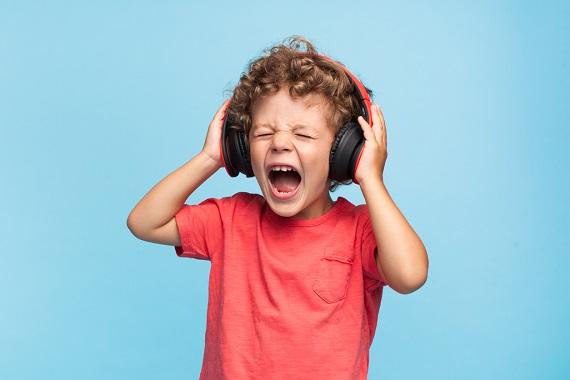 Copil ce asculta muzica la casti la un volum prea ridicat