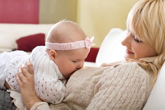 Mama ce isi alapteaza bebelusul stand in pat, rezemata de o perna