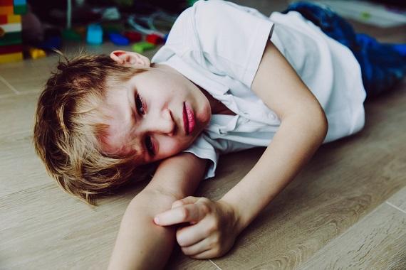 Copil care nu se simte bine si s-a intins pe jos
