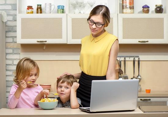 Mama ce sta alaturi de copiii ei cand acestia iau micul dejun