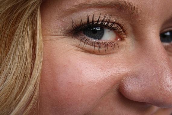 Femeie care zambeste si are riduri in coltul ochilor
