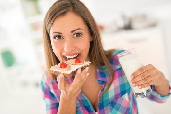 Fata care vrea sa muste dintr-un sandvis si are in mana un pahar de lapte