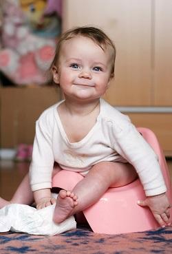 Bebelus pe olita, cu un sul de hartie igienica in mana
