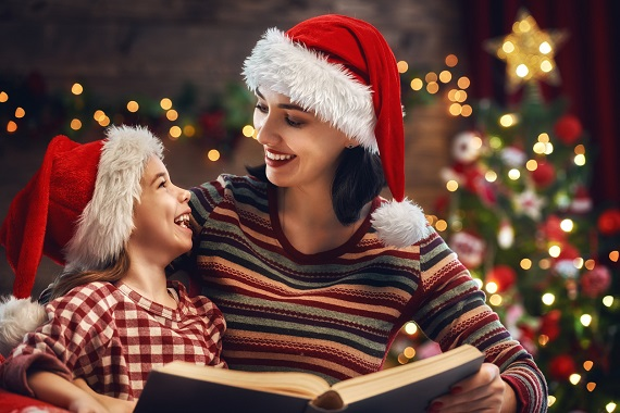Mama si fiica cu caciulite de Mos Craciun, citind o carte