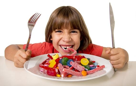 Fetita ce are in fata ei o farfurie plina de dulciuri