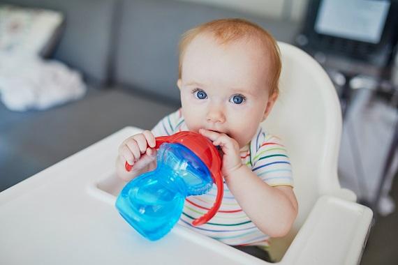 Bebelus aflat in scaunelul sau, ce tine in mana o cana dotata cu manere