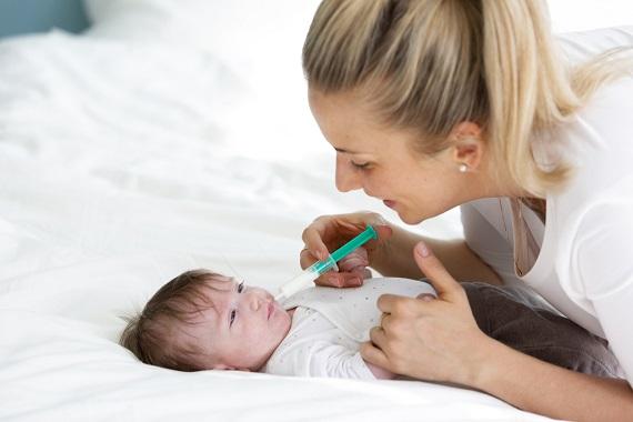 Mama ii da bebelusului lapte cu seringa