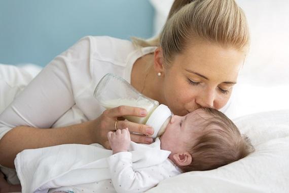 Mama ce ii da bebelusului lapte din biberon