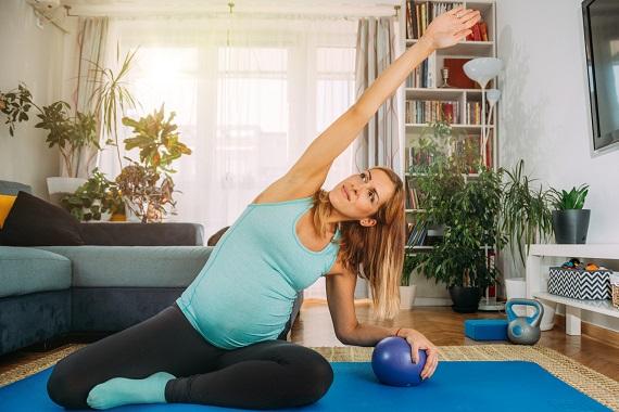 Femeie insarcinata ce face un exercitiu yoga acasa