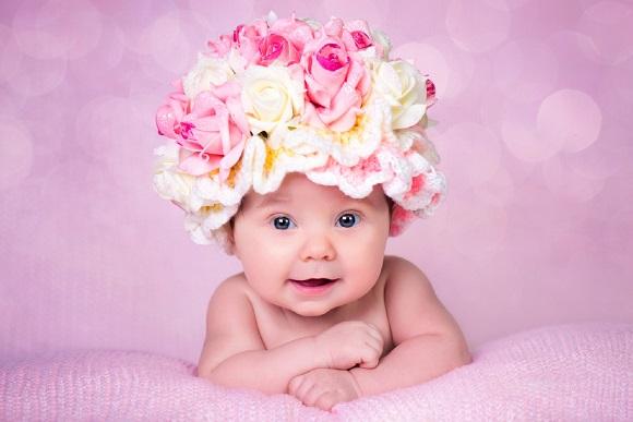 Bebelusa ce ăoarta pe cap o caciulita pe care au fost aplicati trandafiri