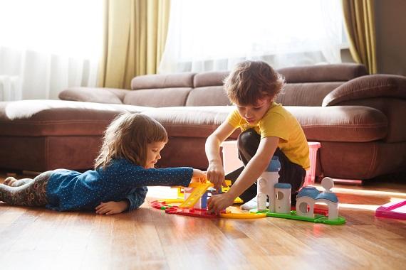 Fetita si baietel care se joaca impreuna cu un set de construit